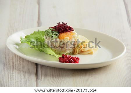 salty fish salad with caviar on wooden background - stock photo