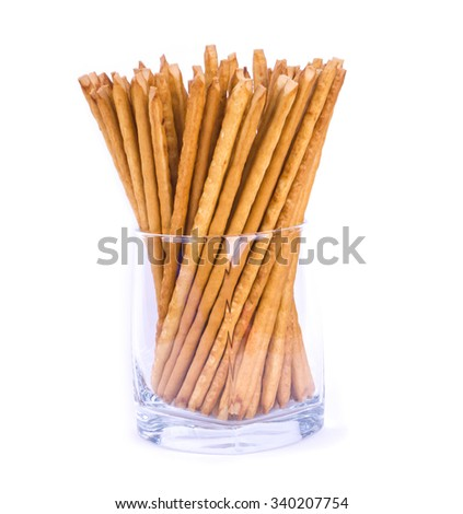 Salty sticks standing in a glass isolated. Sticks in a glass. Crunchy snack. - stock photo