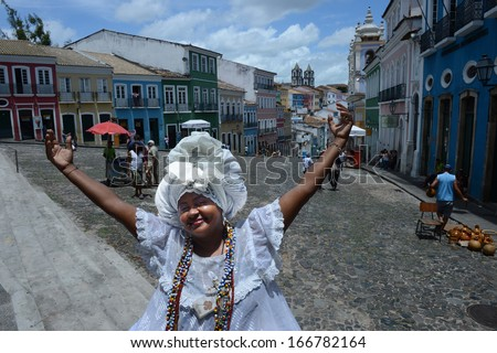 SALVADOR, BAHIA, BRAZIL:09 DEC 2013: A traditional Bahia's woman, called bahiana, open his arms at the Pelourinho square in Salvador on 09th Decenber 2013,in Brazil. - stock photo