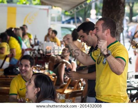 Salvador, Bahia, Brazil - June 28: Cheerful Brazil fans celebrating victory at football match on TV at a bar in Salvador, Bahia, Brazil. - stock photo