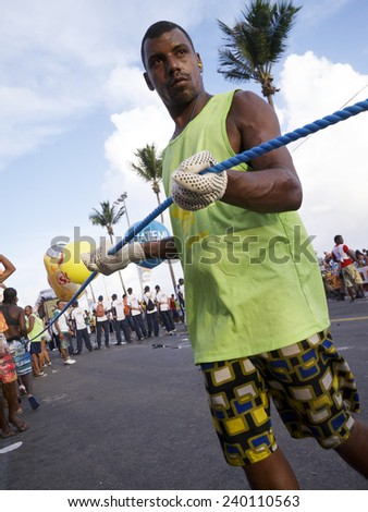 SALVADOR, BRAZIL - FEBRUARY 9, 2013: Brazilian man known as cordeiro holds a crowd control rope alongside a trio electrico music truck on the afternoon Barra Ondina circuit.