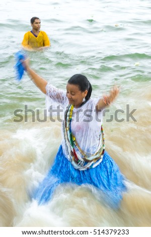 SALVADOR, BRAZIL - FEBRUARY 02, 2016: Worshippers dressed in traditional costume at the Festival of Yemanja wade into the sea at the fishing village of Rio Vermelho. Slow shutter speed motion blur.