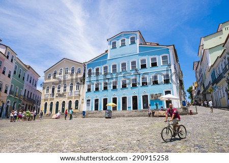 SALVADOR, BRAZIL - MARCH 12, 2015: Brazilian rides bicycle through a plaza surrounded by colonial buildings in the historic district of Pelourinho. - stock photo