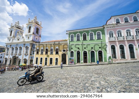 SALVADOR, BRAZIL - MARCH 12, 2015: Brazilians ride scooter through a plaza surrounded by colonial buildings in the historic district of Pelourinho. - stock photo