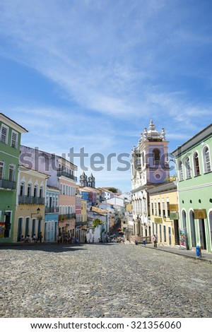 SALVADOR, BRAZIL - MARCH 12, 2015: Pedestrians walk through a plaza surrounded by colonial buildings in the historic district of Pelourinho. - stock photo