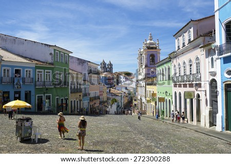 SALVADOR, BRAZIL - MARCH 12, 2015: Tourists cross a plaza surrounded by colonial buildings in the historic district of Pelourinho. - stock photo