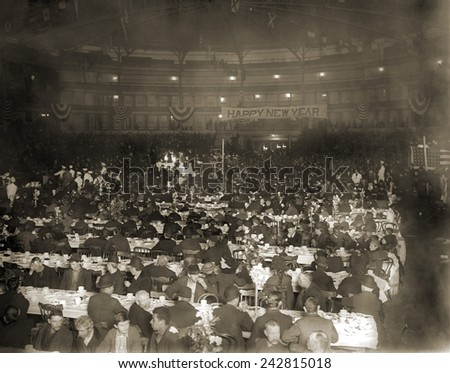 Salvation Army's New Year's Dinner in a large auditorium was attended mostly by men, but also women, children, and African American families, 1910 - stock photo