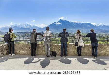 SALZBURG, AUSTRIA - APR 21, 2015: people watch the alps from castle Hohensalzburg in Salzburg, Austria. The mountain peaks are still covered with snow. - stock photo