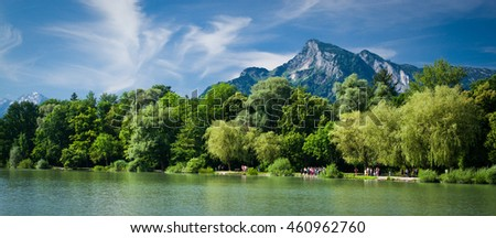 Salzburg, Austria - July 11, 2016: Across a lake (Leopoldskroner Weiher) in Salzburg with the Untersberg in the background, tourists view the Leopold Palace featured in the Sound of Music.