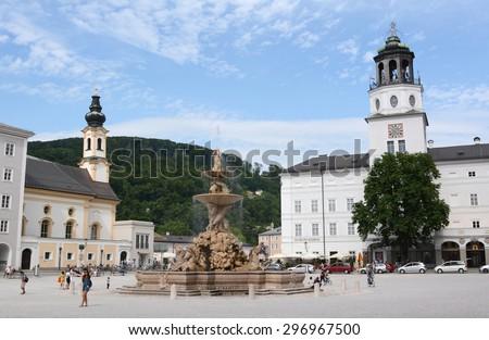 Salzburg, Austria - June 29, 2015: Residenzbrunnen in Salzburg, Austria. Tourists and locals around the Baroque fountain in the Residenzplatz. St. Michaelskirche and the Neue Residenz stand beyond. - stock photo