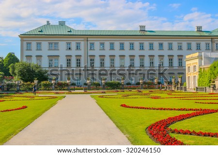 SALZBURG, AUSTRIA -June 25, 2015: view of famous Mirabell Gardens with the old historic Fortress Hohensalzburg. Walk in Park of Flowers , Sunny day. Blue sky and green trees.