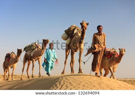 SAM, INDIA - NOVEMBER 28: An unidentified camel man is leading his  camels across the Thar desert near Jaisalmer on November 28, 2012 in Sam, Rajasthan, India. - stock photo