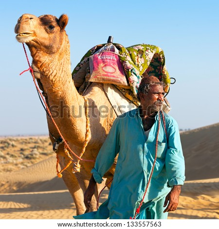 SAM, INDIA - NOVEMBER 28: An unidentified camel man is leading his camels across the Thar desert near Jaisalmer on November 28, 2012 in Sam, Rajasthan, India.