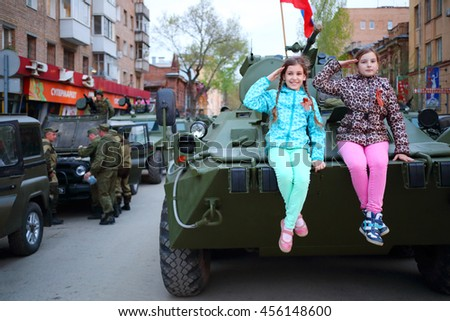 SAMARA - MAY, 6, 2015: Two girls (with model releases) pose on armored vehicle in Samara during military celebration. Red Square is not affected by military equipment on parade May 9th - stock photo