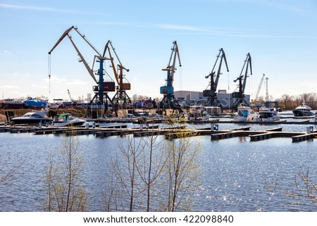 SAMARA, RUSSIA - APRIL 24, 2016: Silhouette of port cranes against the blue sky and motor boats at the Samara river port - stock photo