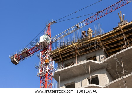 SAMARA, RUSSIA - APRIL 13, 2014:Tall building under construction with crane and workers against a blue sky - stock photo