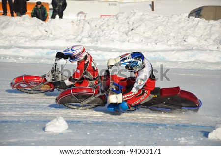 SAMARA, RUSSIA - JANUARY 27: Racing on ice, two unidentified driver on a motorcycle with spikes rotates with a large slope on one knee on the ice speedway Championship January 27, 2012 in Samara, Russia