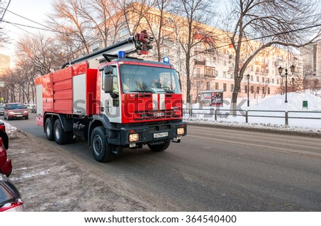 SAMARA, RUSSIA - JANUARY 10, 2016: Red firetruck IVECO speeding down a street to a call