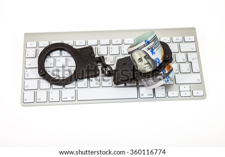 SAMARA, RUSSIA - JANUARY 9, 2016: Steel handcuffs and dollars bill lying on a computer keyboard on the white background - stock photo