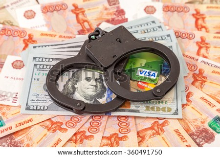 SAMARA, RUSSIA - JANUARY 9, 2016: Steel handcuffs lying on a stack of dollar bills and credit cards on the background of russian rubles - stock photo