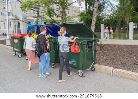 SAMARA, RUSSIA - JUNE 12, 2014: People throws trash in the new plastic dumpster  - stock photo