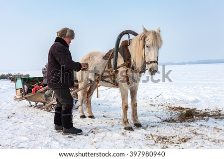 SAMARA, RUSSIA - MARCH 9, 2015: Horseman with horse harnessed in sledge at the bank of frozen river in Russia