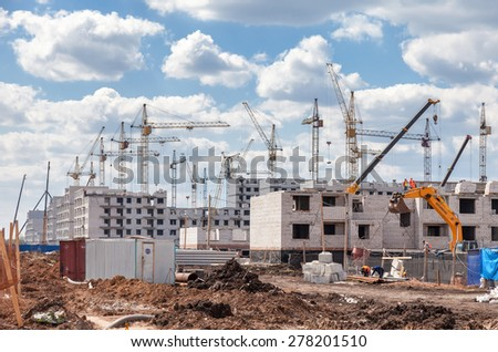 SAMARA, RUSSIA - MAY 11, 2015: Apartment buildings under construction with cranes against a blue sky background - stock photo