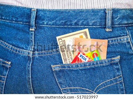 SAMARA, RUSSIA - NOVEMBER 11, 2016: Ten american dollars, ten euro notes and credit cards sticking out of the blue jeans pocket