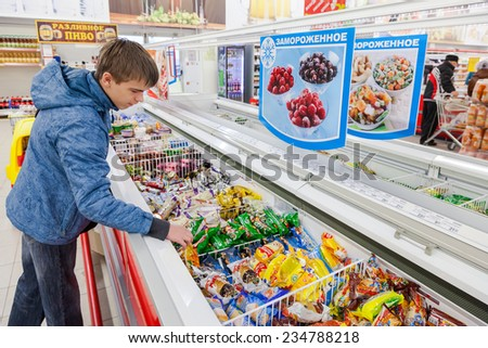 SAMARA, RUSSIA - OCTOBER 5, 2014: Young boy choosing ice cream at shopping in supermarket store Magnit. Russia's largest retailer - stock photo