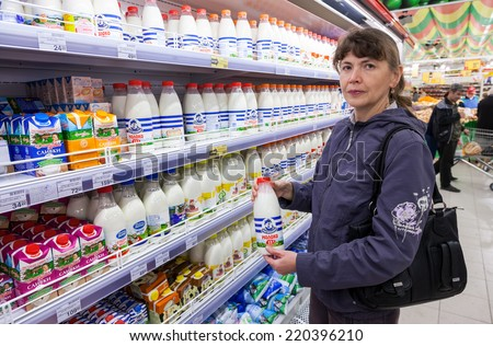 SAMARA, RUSSIA - SEPTEMBER 27, 2014: Young woman choosing fresh milk produces at shopping in dairy supermarket store Magnit. Russia's largest retaile - stock photo