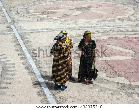 SAMARCAND, UZBEQUISTAN - MAY 26 2011: Local women in typical dresses on the most famous square of Registan