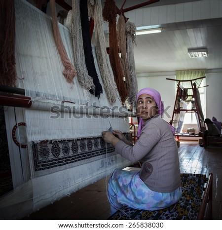 SAMARQUAND, UZBEKISTAN - MARCH 14, 2015: Unidentified female weaver knotting a handmade carpet.  - stock photo