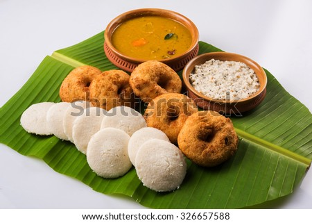 Sambar Vada & Idli with sambar, coconut chutney and red tomato chutney in earthen pots, served over green banana leaf, front view over white background  - stock photo