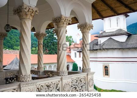 Sambata, Romania - June 24, 2012: Church inside Sambata de Sus Monastery seen trough a colonade in Transylvania, Romania - stock photo