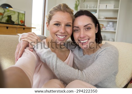 Same sex female couple taking a selfie in their home - stock photo