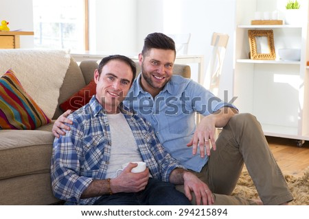 Same sex male couple sitting together in their front room on the floor. One man is holding a coffee whilst the other has his arm round his shoulders.  - stock photo