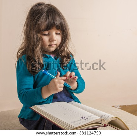 Samll girl inside studio with red copybook in hand - stock photo