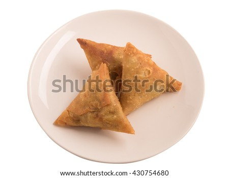 Samosas a spicy blend of vegetables or meat wrapped in a deep fried triangular pastry parcel in a white plate - stock photo