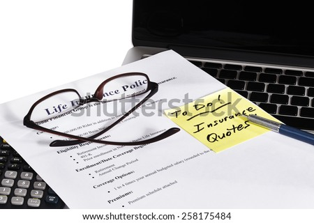 Sample Insurance Policy business document with laptop and calculator and reading glasses and yellow TO DO reminder note on white background - stock photo
