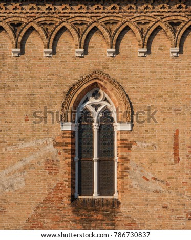 Sample of venetian gothic window on a brick wall