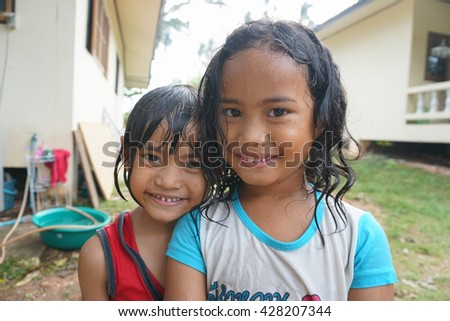 SAMUI ISLAND, THAILAND - 29 MAY 2016: Two Thai girls bathing in yard