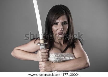 Samurai.Anime stylized brunette with short hair holding a katana sword with two hands - stock photo