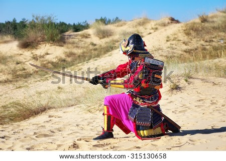 Samurai with sword on the sand. Men in samurai armour on the sand. Original Character - stock photo