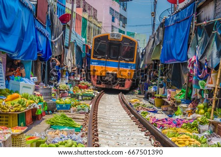 SAMUT SAKORN - APRIL 10 : Photo taken beside the train track where the diesel train was riding through market place at noon April. 10, 2016 in Samut Sakorn, Thailand.