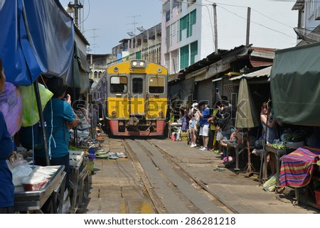 Samut Songkhram, Thailand - Jun 11 2015: Mae Klong Railway Station is one of the tourist place near Bangkok. Every time the train passes the fresh market all vendors have to move the product away.