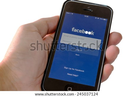 SAMUTPRAKAN, THAILAND - December 28, 2014:man holding brand new black Apple iPhone 5C with loging in Facebook app. Facebook the largest social network in the world.