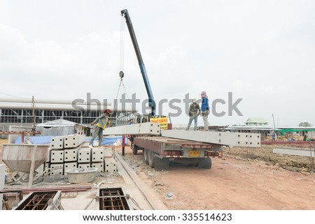 SAMUTSAKHON,THAILAND NOVEMBER 4,2015:Crane truck loading a concrete pillar on construction background.