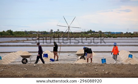 SAMUTSAKORN, THAILAND - APRIL 15, 2013: Unidentified workers keeping salt from Salt farming or Salt evaporation pond to warehouse at Bangkhunthein. - stock photo