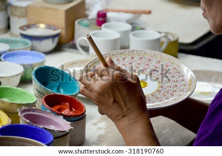 SAMUTSAKORN, THAILAND - AUGUST 8 : Thai people woking process paint Ceramic Benjarong is traditional thai five basic colors style pottery at workshop on August 8, 2015 in Samutsakhon, Thailand.