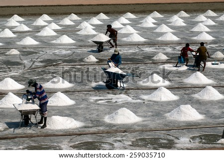 SAMUTSONGKHRAM,THAILAND - FEB 18: Unidentified workers carrying salt at the salt farm on February 18,2014 in Samutsongkhram Province,Thailand.Salt production is one of the main industries in Thailand. - stock photo